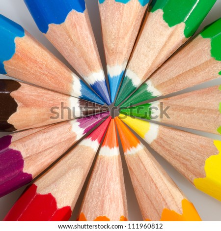 Color pencils arranged in roygbiv on white background - stock photo