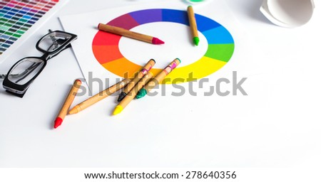 color pencils, colored palette and glasses on wooden table - stock photo
