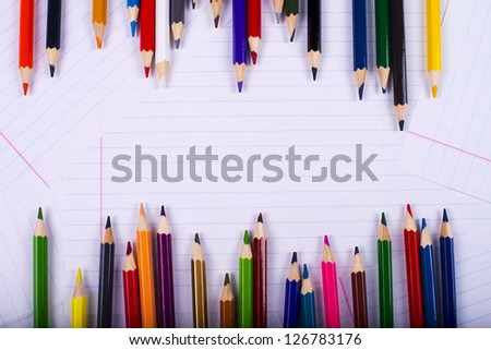 color pencils creating a chaotic frame on a surface from writing-book sheets - stock photo