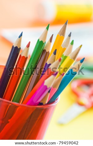 color pencils in glass on desk with shallow depth of field - stock photo