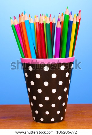 Color pencils in glass on wooden table on blue background