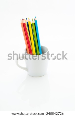 Color pencils in white coffee cup isolated on white background - stock photo