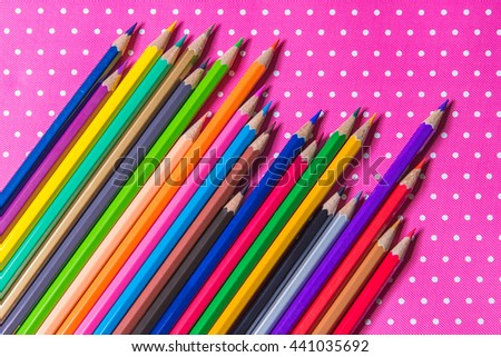 Color pencils isolated on Pink fabric background. - stock photo