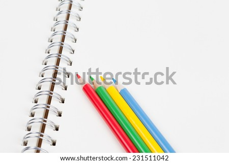 Color pencils on blank notebook - stock photo