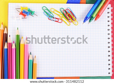 Color pencils on multi-colored paper with notebook - stock photo