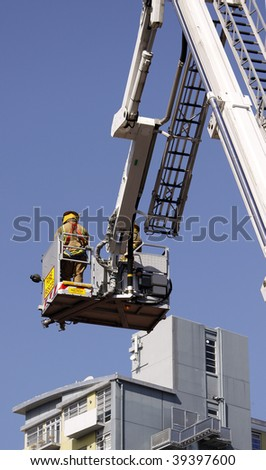 color photo image of firefighter lifted in cherry picker