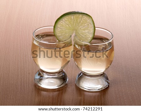 Color photo of a glass cup with tequila and lime - stock photo