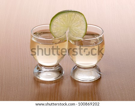 Color photo of a glass of tequila and lemon - stock photo
