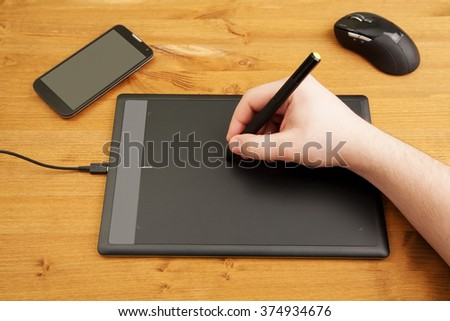 Color photo of a graphic tablet with hand working on it. Top view