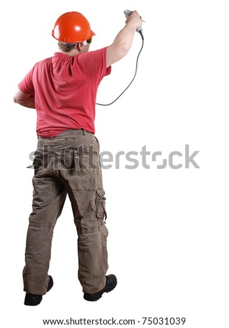 Color photo of a man in work clothes and a helmet with a drill - stock photo