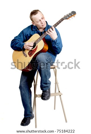 Color photo of a man with an acoustic guitar in his hands