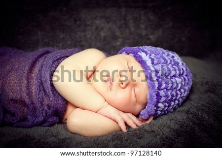 Color photo of a newborn baby boy sleeping peacefully under a soft blanket. Selective focus!
