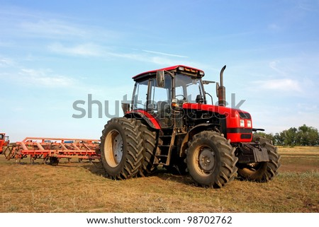 Color photo of a red tractor with a harrow - stock photo