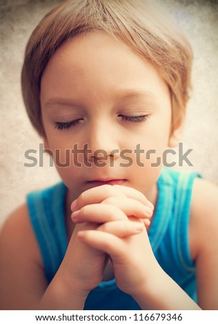 Color photo of a young boy who is praying - stock photo
