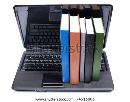 Color photo of an old book and computer - stock photo