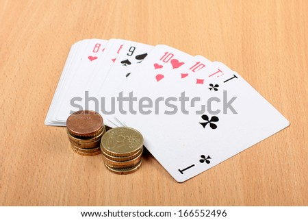 Color photo playing cards and coins on a wooden table