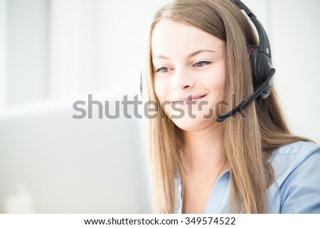 Color picture of a female consultant using headphones - stock photo