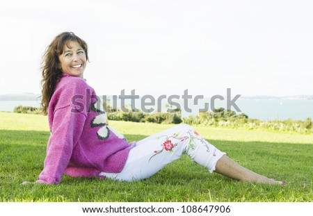 color portrait photo of a beautiful mature woman in her late forties sitting in a grassy park smiling and wearing a bright pink sweater and white jeans. - stock photo