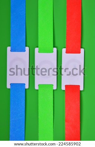 color rfid id bracelets on a green background - stock photo