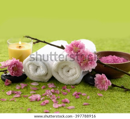 color sea salt in wooden bowl with flower candle on green towel - stock photo