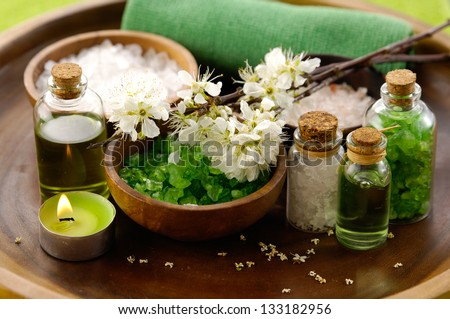 color sea salt in wooden bowl with salt in glass , cherry, candle, massage oil - stock photo