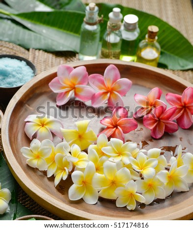 color sea salt with frangipani in wooden bowl with, oil ,salt on mat