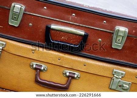 Color shot of a pile of old, used suitcases. - stock photo