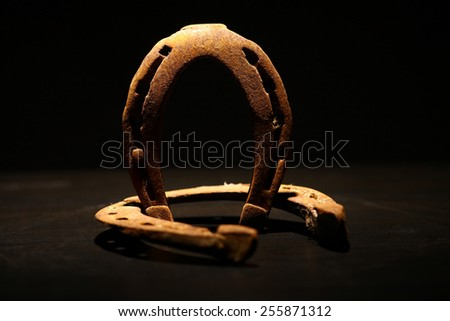 Color shot of two rusty horse shoes on a dark background. - stock photo
