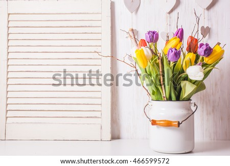 Color tulips with branches in a white cane. Spring decor