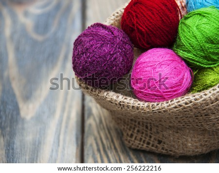 color woolen clews for knitting in burlap bag on old wood table - stock photo