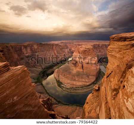 Colorado River snakes around the sandstone cliffs of Horseshoe Bend, with a storm on the horizon - stock photo