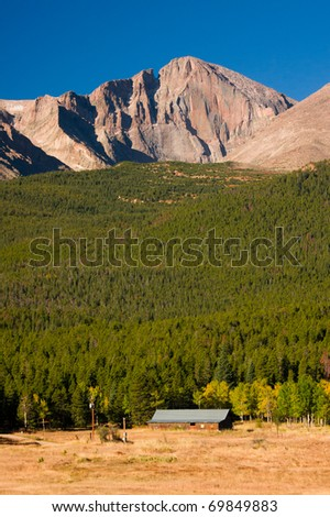Colorado's Longs Peak stands above an old historic cabin - stock photo