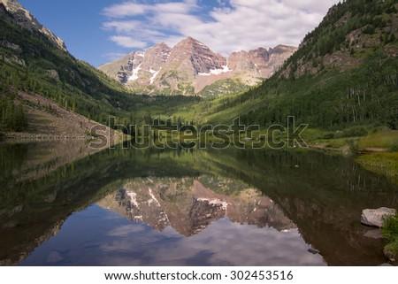 Colorado's Maroon Bells reflected in Maroon Lake, summer near Aspen - stock photo