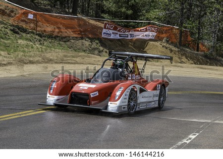 COLORADO SPRINGS, CO - JUNE 30: Greg Tracy #34 drives a Mitsubishi MiEV Evolution II to 3rd place in the Electric Class at the Pikes Peak International Hill Climb on June 30, 2013 in Colorado Springs. - stock photo