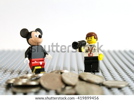 Colorado, USA - May 13, 2016: Studio shot of LEGO minifigure Mickey Mouse with a movie director and a pile of money.  - stock photo