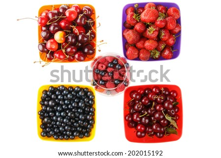 colored berries in bowls and white background