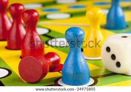 Colored board game figures with dice - stock photo