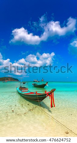 Colored boats on the beach with turquoise water under the clouds.