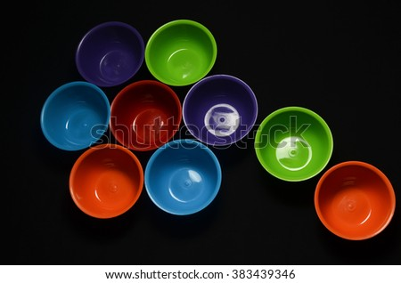 Colored bowls on a black background - stock photo