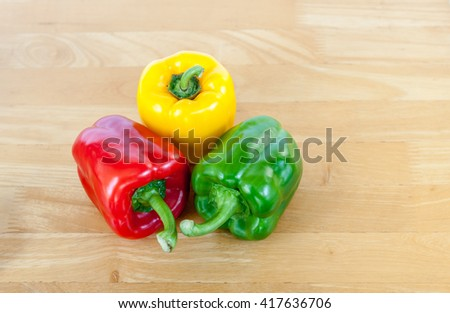 Colored capsicum or bell peppers on the cutting board.  - stock photo