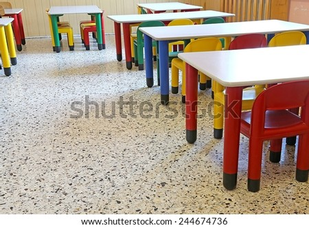 colored chairs and small tables in the dining room of the nursery - stock photo
