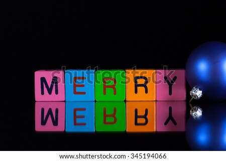 Colored children's cubes and Christmas decoration on a black glass desk