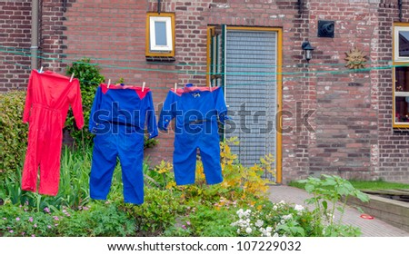 Colored children's overalls on the clothesline of a Dutch care farm. - stock photo