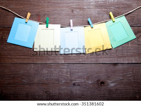 Colored clothespins with photo frames on rope on a wooden table or board for background. Space for text. - stock photo