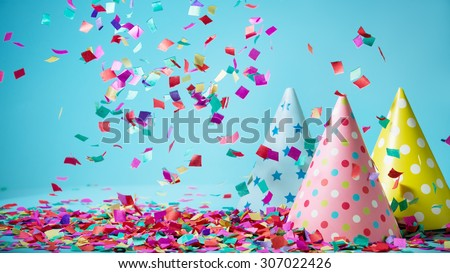 Colored confetti and party hat on blue background - stock photo