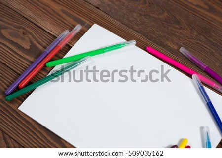 colored crayons and a sheet of paper notebook on a wooden background table, creative concept Rustic