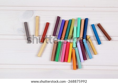 Colored crayons on wood background - stock photo