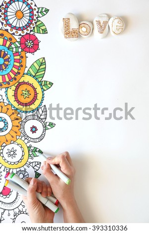 Colored doodle flowers painted on a white background. Markers lie on a white background. View from above. White stones painted color patterns. Hand painted art markers, color patterning.