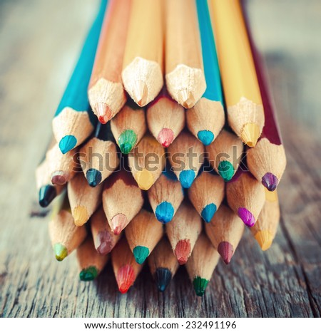 Colored drawing pencils closeup on old desk. Vintage stylized image. - stock photo