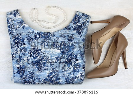 colored dresses with beads and shoes on wooden table - stock photo